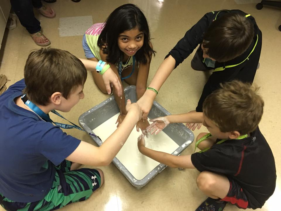 kids on floor doing experiment with hands in a tub
